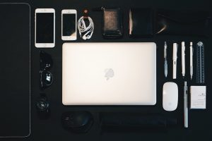 Photo of a carry case for digital items with laptop, mouse, phones, cables, pens by Samule Sun on Unsplash -